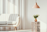 Pastel orange lamp above white flowers in glass vase on trendy openwork table in bright living room interior with white couch