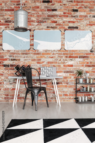 Maps on brick wall of industrial home office with metal furniture and black and white rug on the floor - 238383129