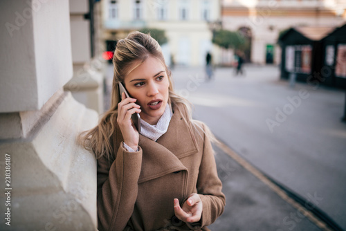 obraz lub plakat Elegant young woman talking on mobile phone in the city street.