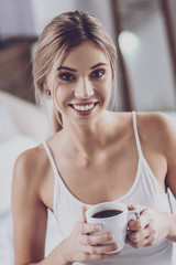 Blonde woman drinking coffee at home