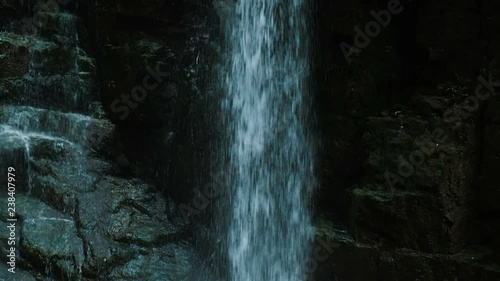 Super slow motion of a waterfall, water falls down in Georgia in a park in summer rain, camera movement