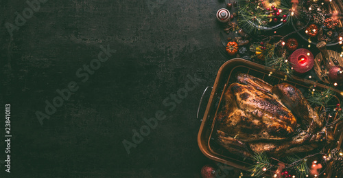 Whole roasted turkey, stuffed with dried fruits in roasting pan for Christmas dinner, served on dark table background with decoration and candles,  top view , banner. Copy space for your design