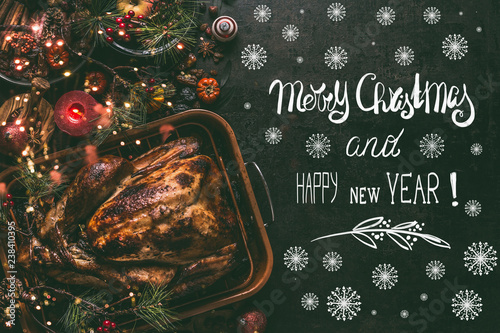 Merry Christmas and Happy New Year greeting card with text , whole roasted turkey on Christmas dinner table background with decoration and burning candles,  top view - 238410395
