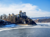Medieval castle in Niedzica, Poland, in winter at partially frozen artificial Czorsztyn lake on Dunajec river and the far view of Czorsztyn castle. Sunset light