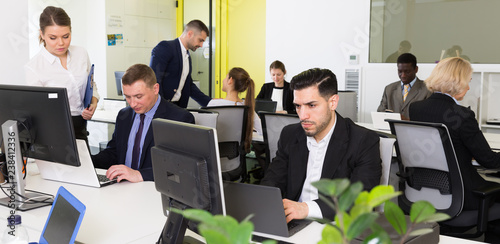 Coworkers engaged in open plan office