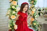 beautiful little girl in red dress sitting on a swing with flower decor