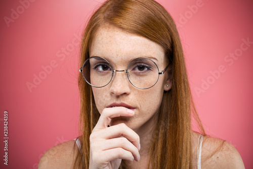 Leinwanddruck Bild Interesting young woman with eyeglasses thinking and looking at camera over pink backgound.