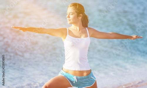Fototapeta Młoda kobieta uprawiania jogi na plaży