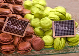 Colorful traditional chocolate and pistachio macaron pastries in a bakery shop the south of France