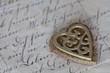 little golden nostalgic heart on historic letter
