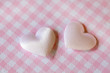 small pink satin hearts on pink plaid pattern background