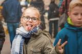 Glückliches verrücktes Kind schneidet lustige Grimasse und zeigt Handzeichen für Frieden