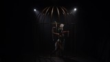 Graceful girl gymnast riding a hoop in a cage on dark stage. Black background. Slow motion - 238448104