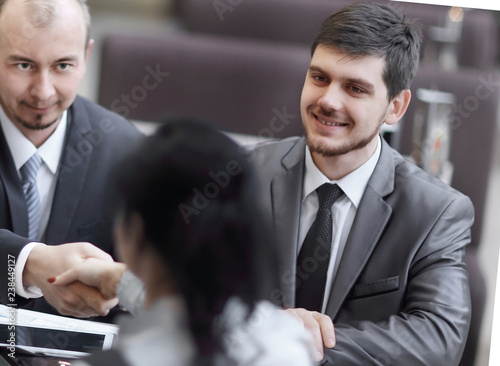 Manager and customer handshake sitting in Bank office