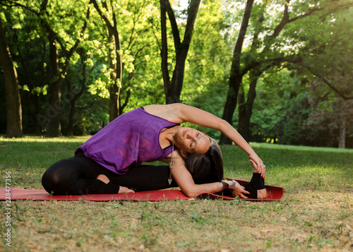 Fototapeta Beautiful female stretching in park on yoga mat