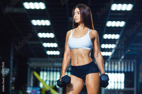 Foto Murales Young fit woman in sporty shorts and top holding dumbbells while standing in the gym