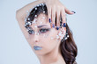 Beautiful model girl with blue manicure nail design,face and hair with beads, rhinestones ,decoration. Fashion makeup and care for hands and nails and cosmetics.Nail art design.emale beauty. Luxury