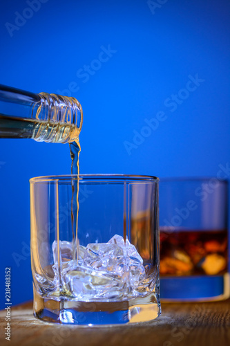 Whiskey is poured in a glass with ice on a blue background