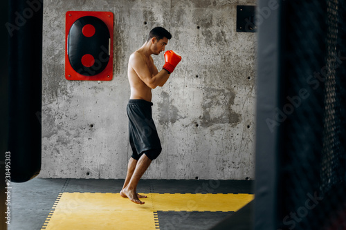 Sportsman with a naked torso and in the red boxing gloves hits equipment for boxing on a concrete wall in the gym