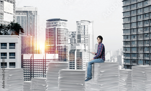 Attractive man sitting on pile of paper documents. - 238500513