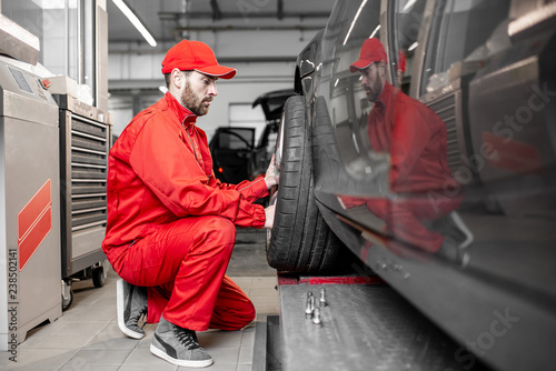 Two Car Service Workers In Red Uniform Changing Wheel Of A Sport Car