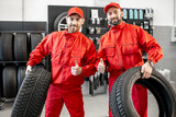 Portrait of a two car service workers in red uniform standing together with new tires at the store