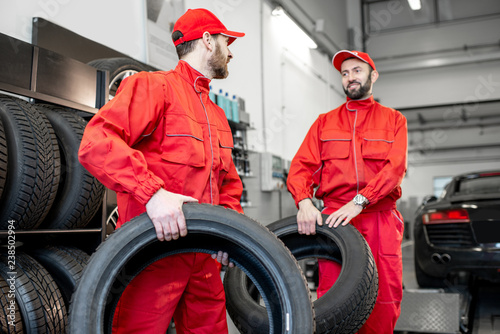 Car Service Workers In Red Uniform Carrying New Tires At The Tire