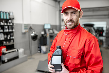 Portrait of a handsome auto mechanic in red uniform holding bottle with engine oil at the car service