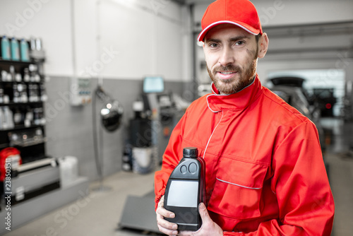 fototapeta na ścianę Portrait of a handsome auto mechanic in red uniform holding bottle with engine oil at the car service