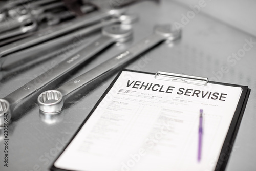 Foto Murales Vehicle service agreement on the table with stainless wrenches indoors