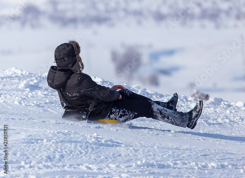 The boy rides a sled from the mountain in winter