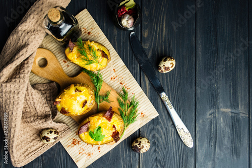 baked potato stuffed with cheese and bacon on paper on wooden background - 238511989