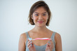 Portrait of smiling young woman holding toothbrush. Asian girl advertising new toothbrush. Dental care concept