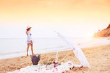 Picnic, relaxing on a wild beach and a blurred silhouette of a girl strolling along the beach in the background. Vintage style photo.