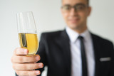 Closeup of business man toasting. Blurred person celebrating event. Holiday concept. Isolated cropped front view on white background. - 238535394