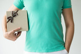 Closeup of man holding gift box under armpit. Person wearing t-shirt. Gift concept. Isolated cropped front view on white background. - 238535924
