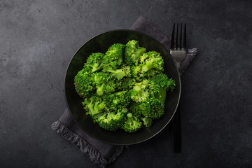 steamed broccoli with sesame seeds in black bowl
