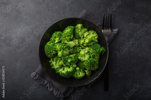 steamed broccoli with sesame seeds in black bowl - 238536573