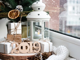 Beautiful Christmas lamp with a candle on the window. Christmas tree, gifts - bracelets and charms. New Year's and Christmas. Postcard. Congratulations.