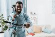 african american man carrying bicycle and smiling in living room