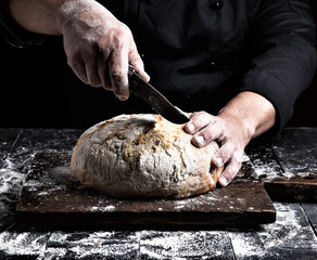 man cuts with a knife a round whole loaf of white wheat flour