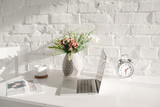laptop near business newspaper, cup and vase with flowers in kitchen - 238557794