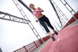 Morning workout. Full length rear view of young womanin sports clothing exercising while jogging on the bridge outdoors