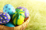 Rustic style painted easter eggs in basket on green background - 238561112