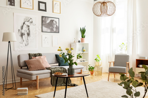 Flowers on wooden table next to grey couch in living room interior with lamp and posters. Real photo