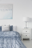 Vertical view of white stylish lamp on bedside table in luxury bedroom interior with velvet blue bedding and painting on the wall - 238561587