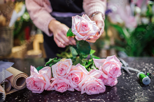 Leinwanddruck Bild Close of beautfiul light pink roses lying on table. Florist hold one flower in hand. Paper rolld and coil with green thread are on table.