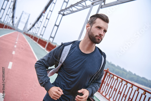 Morning workout. Close up of young man in sports clothing exercising while jogging on the bridge outdoors