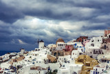 View over Oia village, Santorini island in Greece, on a sunny day with dramatic sky. Scenic travel background.