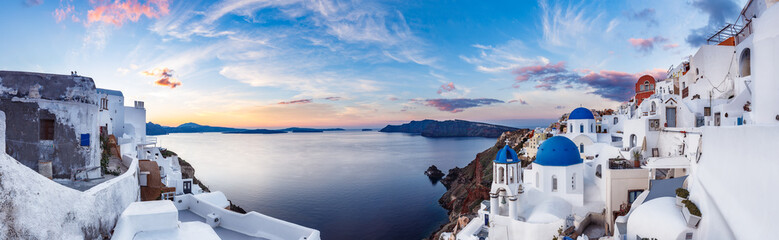 Beautiful panorama view of Santorini island in Greece at sunrise with dramatic sky. © Funny Studio